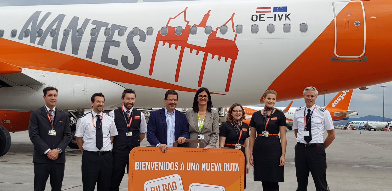 Cristina Echeverría, Directora del Aeropuerto de Bilbao, y Javier Gándara, Director General de easyJet en España, posan con la tripulación del primer vuelo de la ruta Nantes Bilbao delante del avión dedicado a la ciudad francesa y su emblemático Castillo de los Duques de Bretaña